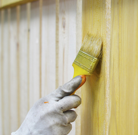 Painting wooden fence with yellow paint